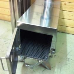 Lavvuovn rustfrit stål, løs askeskuffe. Indfyring og trækregulering i enden af ovnen. Skorsten med gnistfang.